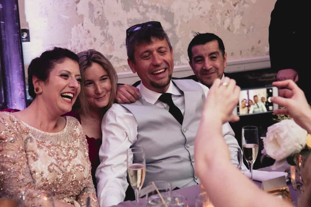 bride and groom having photo taken with guests at unique wedding venue