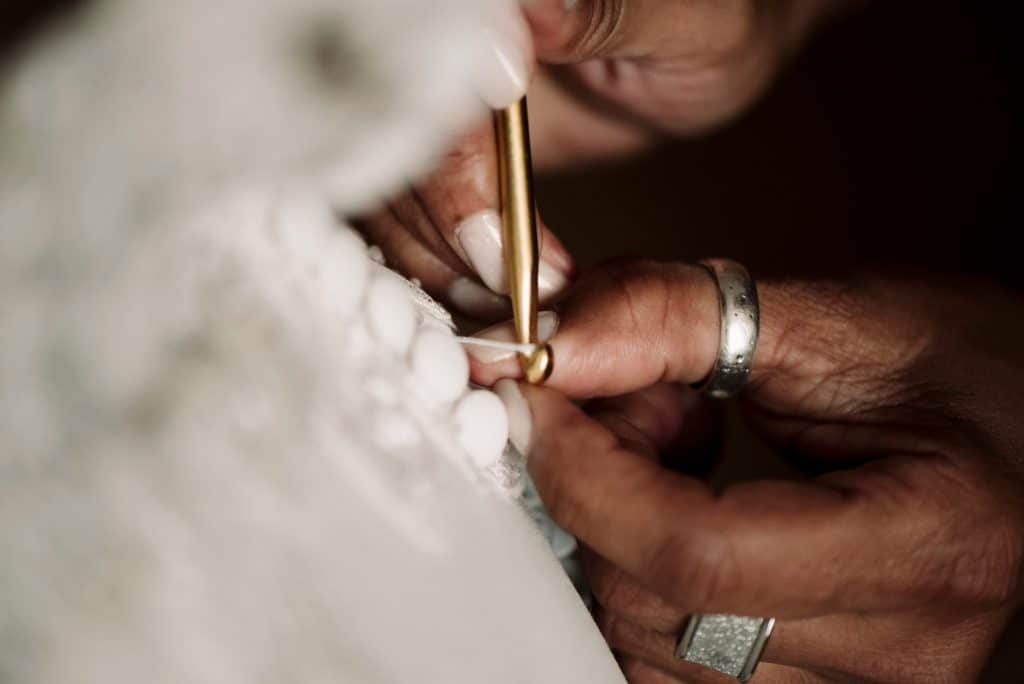detail of wedding dress being fastened