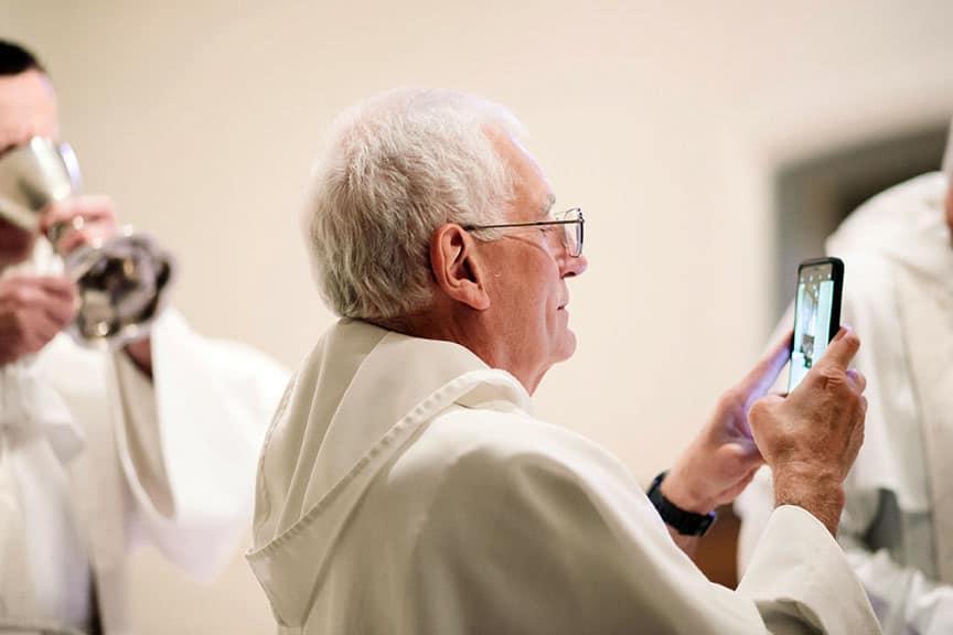 Priest taking selfie at wedding