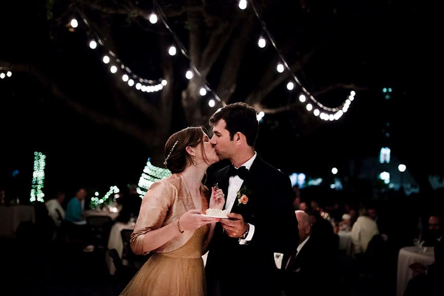 Bride and groom kissing whilst holding wedding cake
