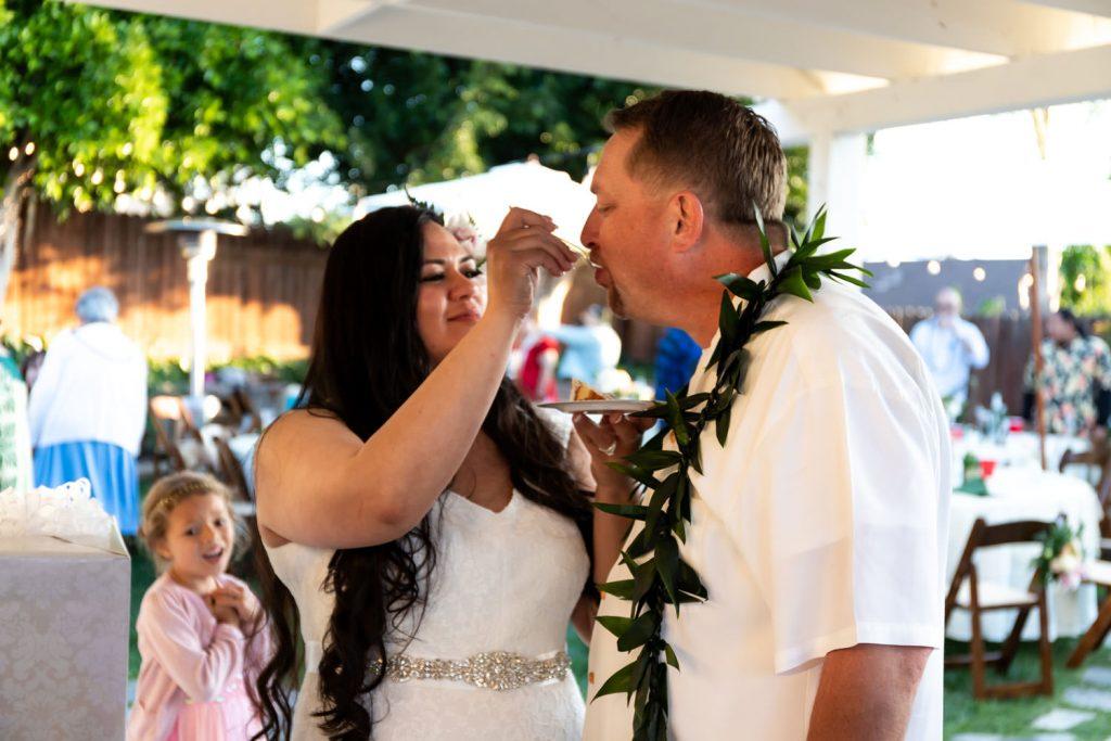 hawaiian bride feeds groom wedding cake