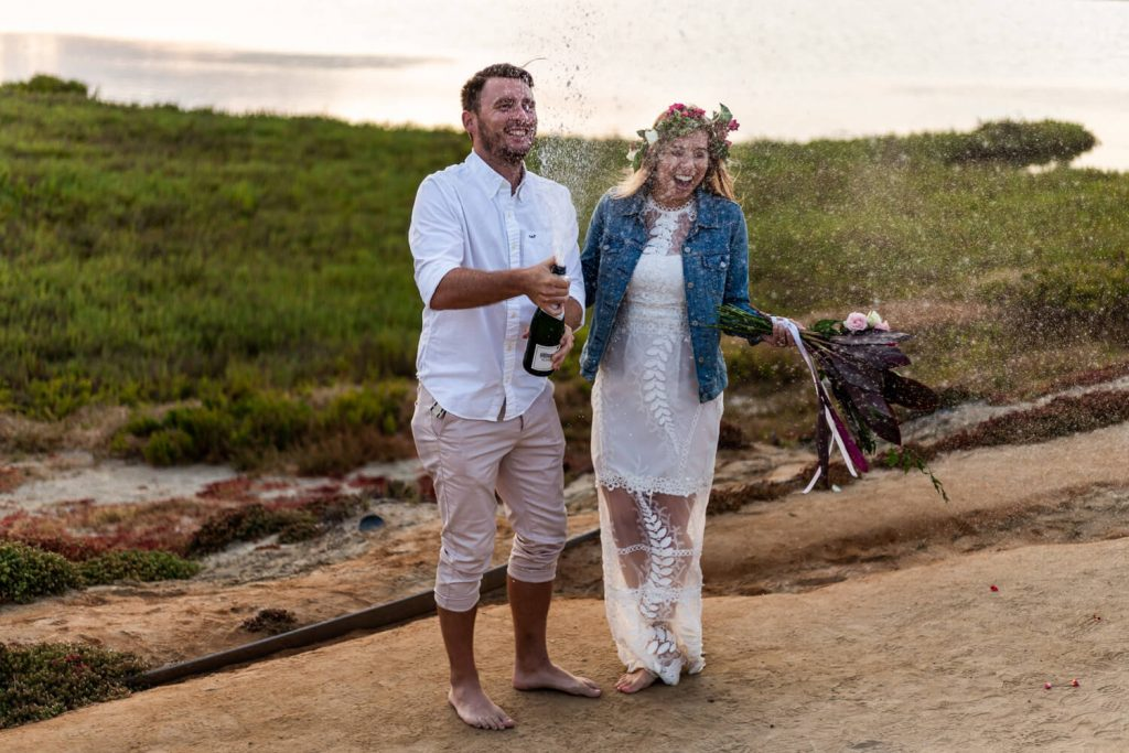 newlyweds open champagne during elopement