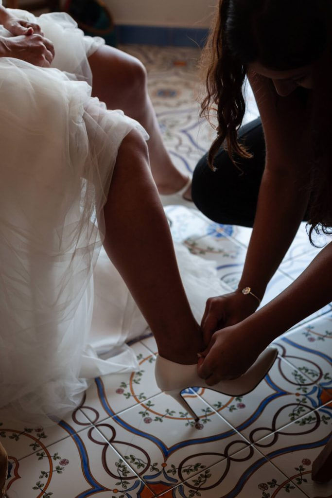 close up of bride putting shoes on