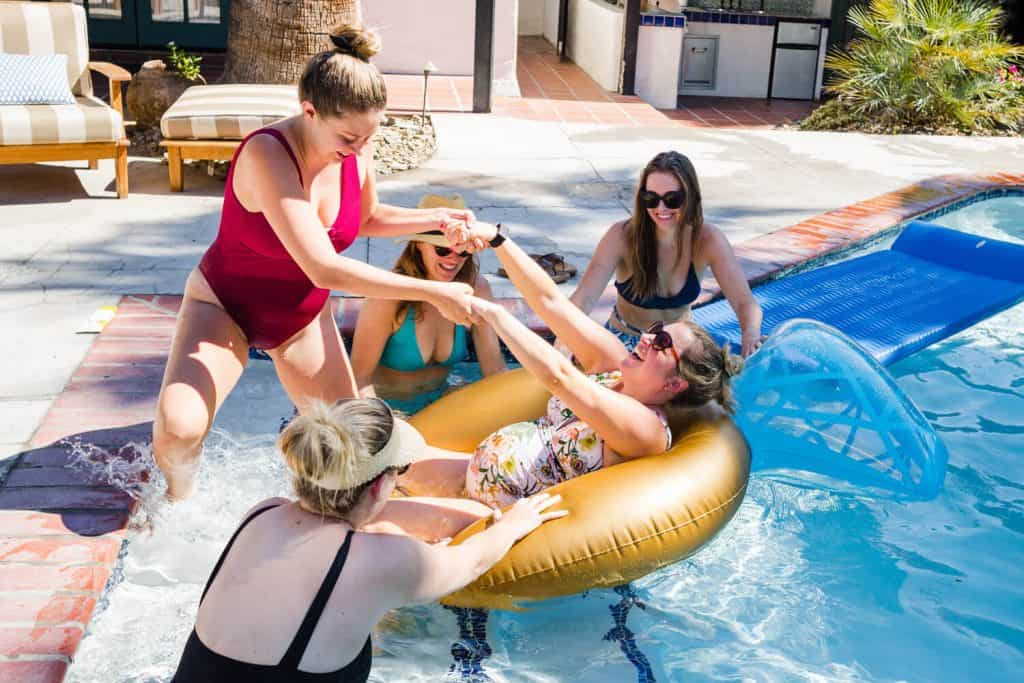 pregnant woman laughingly helped from swimming pool