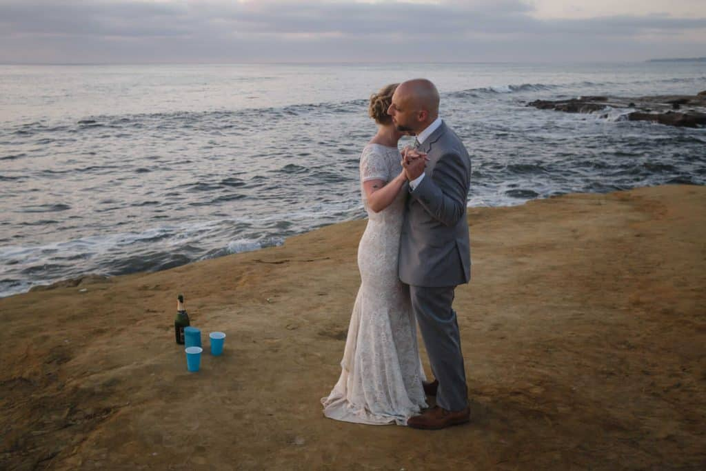 bride and groom dance on cliff side