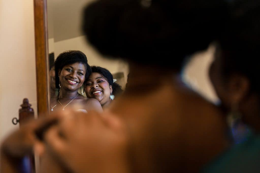 bride and sister hug in the mirrors reflection