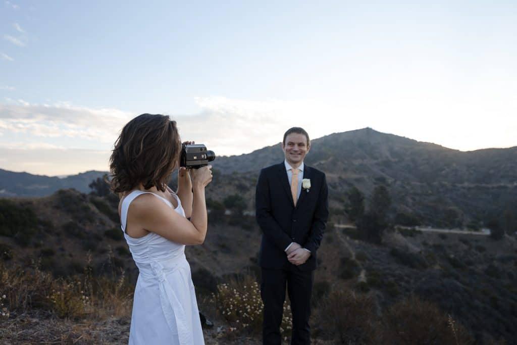 bride films groom with video camera